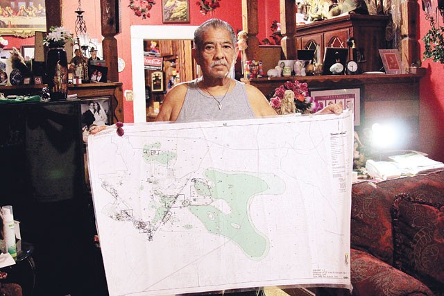 Toxic Triangle resident Robert Alvarado with a map of the contaminated groundwater plume. - MICHAEL BARAJAS