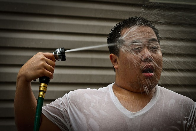 A man seeks relief from the heat by blasting himself in the face with a garden hose. - INSTANT VINTAGE