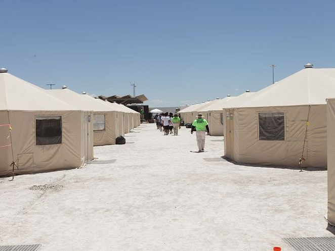Staff and detainees walk between the tents inside the Tornillo, Texas, detention center. - U.S. DEPARTMENT OF HEALTH AND HUMAN SERVICES