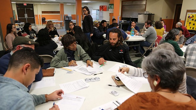 Vallerie Hartfield (left) and Stephen Lucke discuss a question presented to attendees of a city-hosted displacement policy meeting Jan. 16 at the Ella Austin Community Center. - BEN OLIVO / HERON