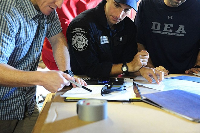 A Coast Guard official transfers chain of custody of seized narcotics to DEA agents. - LAUREN JORGENSEN