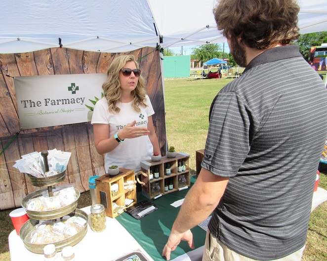 Carolyn Leeper of the Farmacy Botanical Shop discusses her product line at an outdoor mar- ket on the South Side. - SANFORD NOWLIN