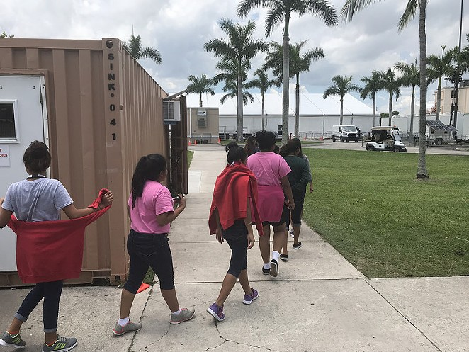 Unaccompanied minors walk inside a facility supervised by the Office of Refugee Resettlement in Homestead, Florida. - DEPARTMENT OF HEALTH AND HUMAN SERVICES