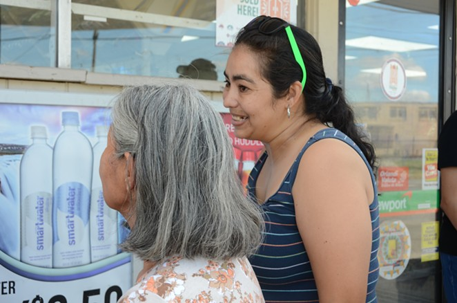 District 3 resident Selena Salazar visits with other residents outside the Gas N' Go store on Wednesday, Sept. 25, 2019. - LEA THOMPSON