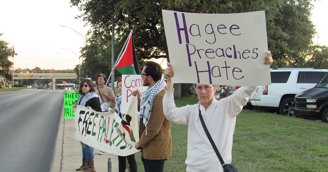 Protestors hold up signs and banners outside of Pastor John Hagee's Cornerstone Church. - SANFORD NOWLIN