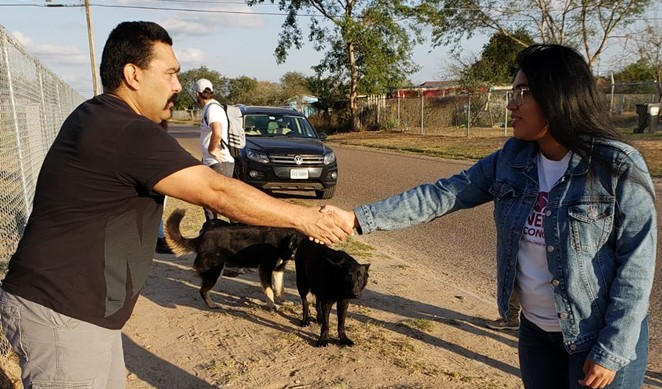 Jessica Cisneros (right) shakes the hand of a potential voter near Mission, Texas. - TWITTER / @JCISNEROSTX