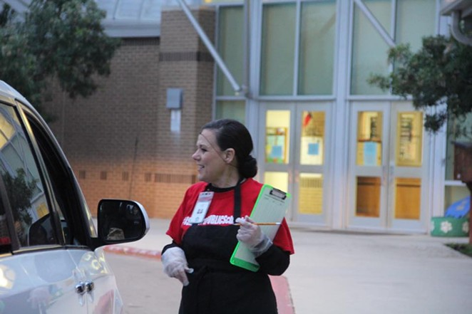 A cafeteria worker with Schertz-Cibolo-Universal City ISD helps with curbside meal pickup. - WE GO PUBLIC