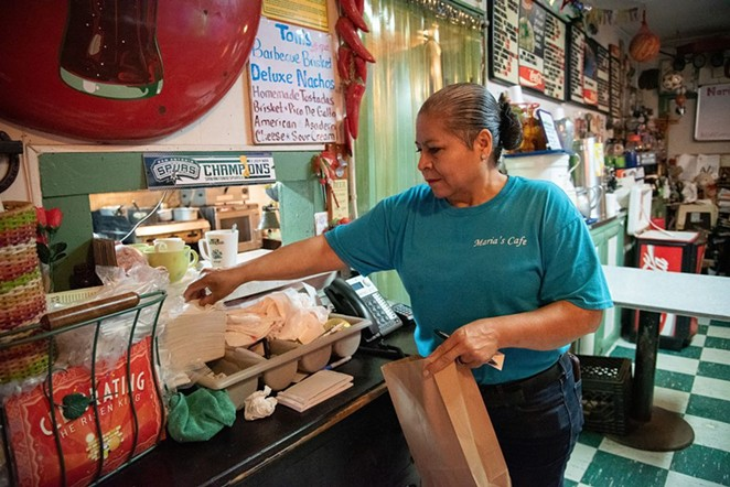 Maria Beza, owner of Maria's Cafe on Nogalitos Street, completes an order on Thursday. - V. FINSTER | HERON CONTRIBUTOR
