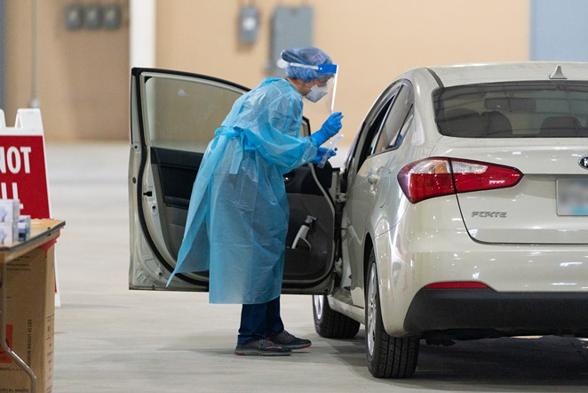 A worker at a drive-through testing facility in San Antonio prepares to collect a sample from someone in a vehicle. - COURTESY PHOTO / CITY OF SAN ANTONIO