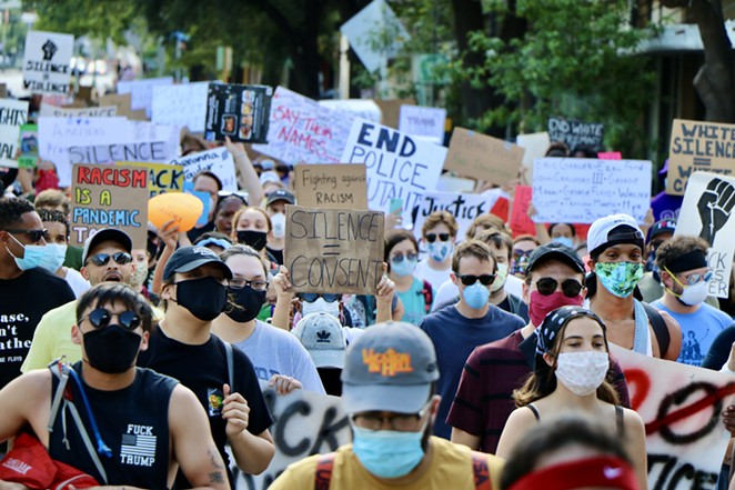 Protesters move through the streets of Downtown San Antonio over the weekend. - JAMES DOBBINS