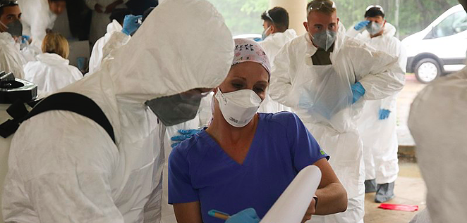 A medical worker performs a COVID-19 screening for National Guardsmen as they prepare to clean a Texas nursing home last month. - WIKIMEDIA COMMONS / THE NATIONAL GUARD