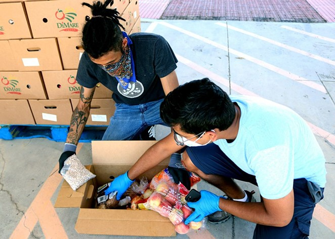 Volunteers Ashanti Williams (left), 30, and Saurau Majumdar, 29, sort through boxes of food at Eco Centro at San Antonio College on June 24. Each box contain apples, oranges, onions, potatoes, carrots and a pound of pinto beans. - ANDREA MORENO / HERON CONTRIBUTOR