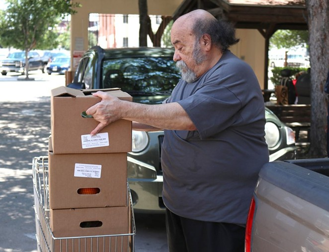 Pancho Valdez, 68, places boxes of DiMare Fresh onto the cart to distribute to tenants under 60 at the Lofts at Marie McGuire Apartments at 211 N. Alamo St. The boxes were delivered by the Coalition for Food Justice. - PHOTO BY ANDREA MORENO / HERON CONTRIBUTOR
