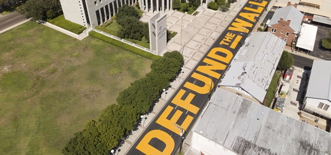 """Laredo's """"Defund the Wall"""" mural decorates the street in front of the border city's federal courthouse. - COURTESY PHOTO / JULIAN ROTNOFSKY"""