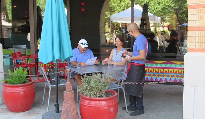 A server at a restaurant at the Pearl development takes an order from diners earlier this summer. - SANFORD NOWLIN
