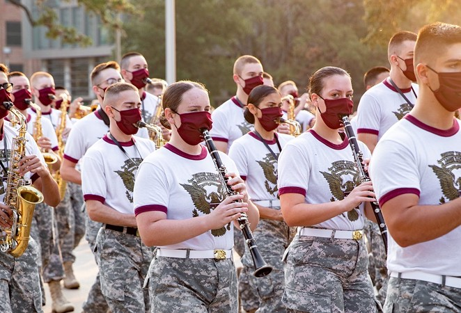 Members of the Aggie Band march through the Texas A&M campus while wearing masks. - TWITTER / @AGGIECORPS