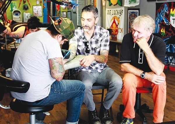 Steve Candelario of Mr. Luckys Tattoo does a tune up on Ricky Armendariz's arm as Gary Sweeney looks on. - COURTESY