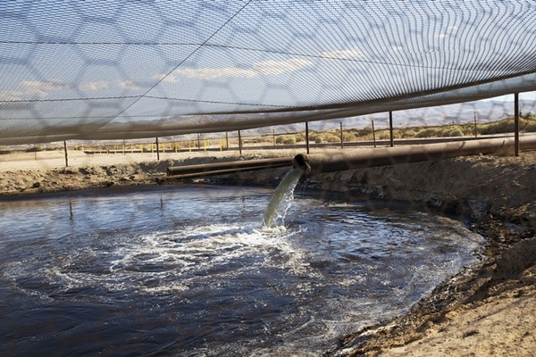 Fracking fluid and other drilling wastes are dumped into an unlined pit located right up against the Petroleum Highway in Kern County, California. - ARAH CRAIG/FACES OF FRACKING