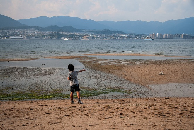 A child plays next to a lake. - FLICKR CREATIVE COMMONS