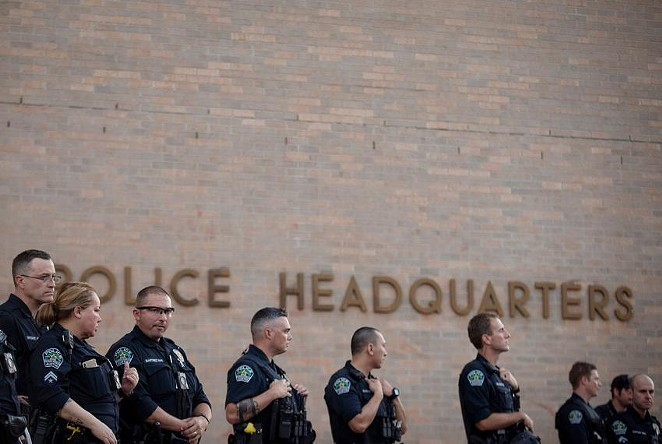 Austin police officers stand guard outside of their headquarters during a protest over the death of George Floyd. Floyd died during an attempted arrest by Minneapolis police. - MIGUEL GUTIERREZ JR. / THE TEXAS TRIBUNE