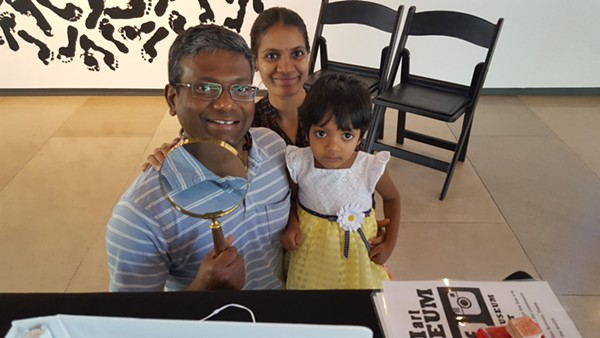 """A family in Phoenix makes use of the Mini Art Museum's magnifying glass to view the wee works in """"Slanguage: Chicos Pero Locos"""""""