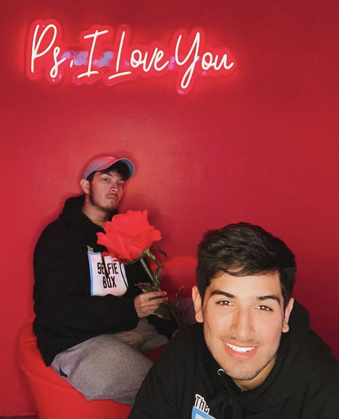 Cesar Ramos (left) and Michael Reyes smile for a photo inside The Selfie Box's red room of love. - COURTESY OF MICHAEL REYES