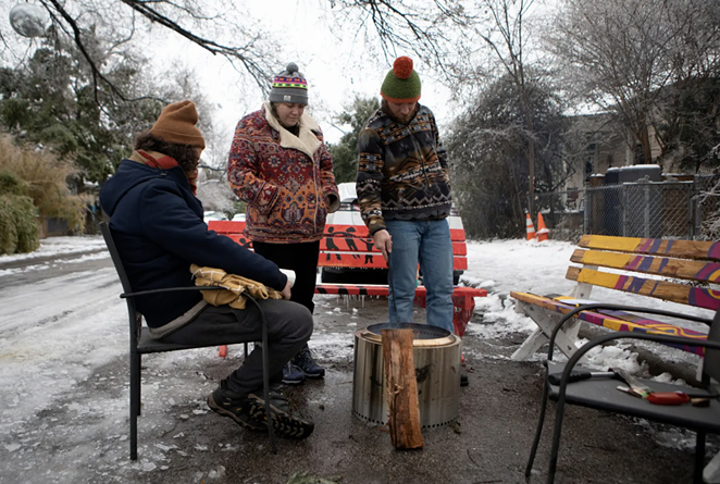 From left: Martin Xoxa, Chelsea Pursley and Joe Williams build a fire on Thursday to keep warm outside of Pursley's home in East Austin. The group had been without power since Monday evening. - MIGUEL GUTIERREZ JR. / THE TEXAS TRIBUNE