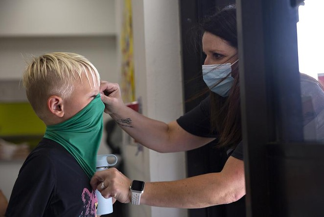 Teachers ensure students have their masks on correctly on the first day of in-person classes at Highland Village Elementary. - SHELBY TAUBER / TEXAS TRIBUNE