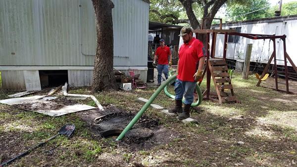 Maintenance staff clean up raw sewage outside an Oak Hollow home. - CITY OF SAN ANTONIO / RAY GARZA