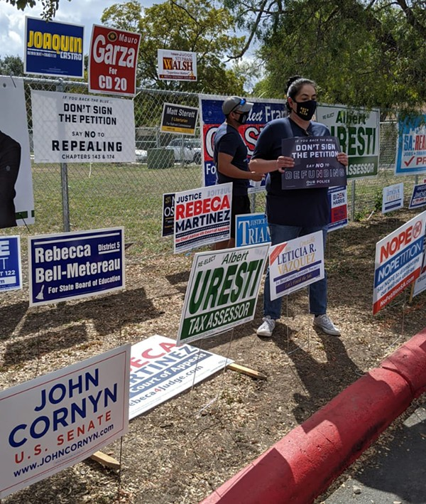 Opponents of Fix SAPD's petition drive hold up signs at a polling site where volunteers collected signatures last fall. - COURTESY OF FIX SAPD