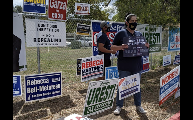 Opponents of Fix SAPD's petition drive hold up signs at a polling site where volunteers collected signatures last fall. - COURTESY PHOTO / FIX SAPD