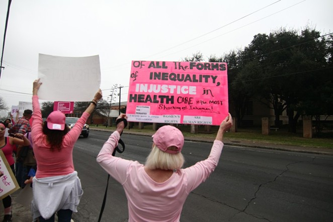 Protesters hold signs at a pro-Planned Parenthood rally in San Antonio. - MICHAEL BARAJAS
