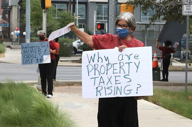 Rebecca Flores protests public facility corporations outside the H-E-B SoFlo Market on Saturday.