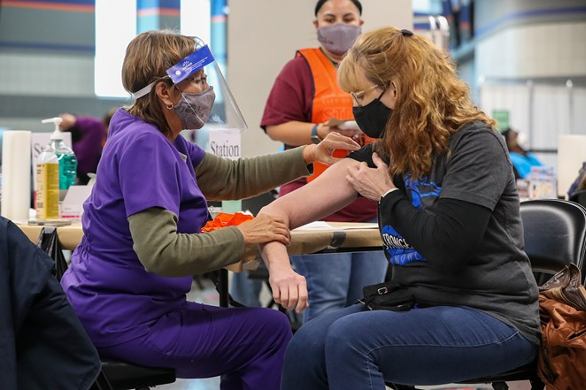 A woman receives her COVID-19 vaccination at the Alamodome. - COURTESY IMAGE / CITY OF SAN ANTONIO