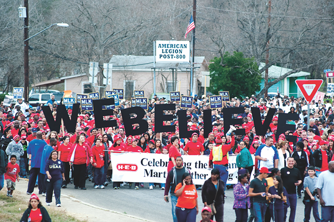 """H-E-B employees carry a sign reading """"WE BELIEVE"""" at San Antonio's Martin Luther King Day march. - SARAH BROOKE LYONS"""