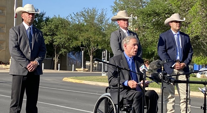 Ranger Dick: Gov. Greg Abbott reads from a speech in front of Freeman Coliseum as members of the Texas Rangers stand behind him. - SANFORD NOWLIN