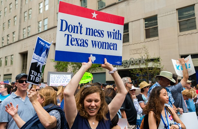 A protester carries a sign defending women's reproductive rights. - SHUTTERSTOCK