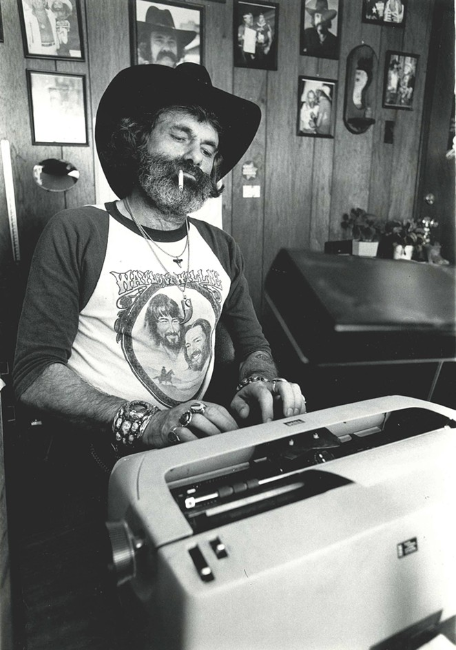 Action Magazine's Sam Kindrick, pictured sitting at a typewriter. - SAM KINDRICK COLLECTION, THE WITTLIFF COLLECTIONS