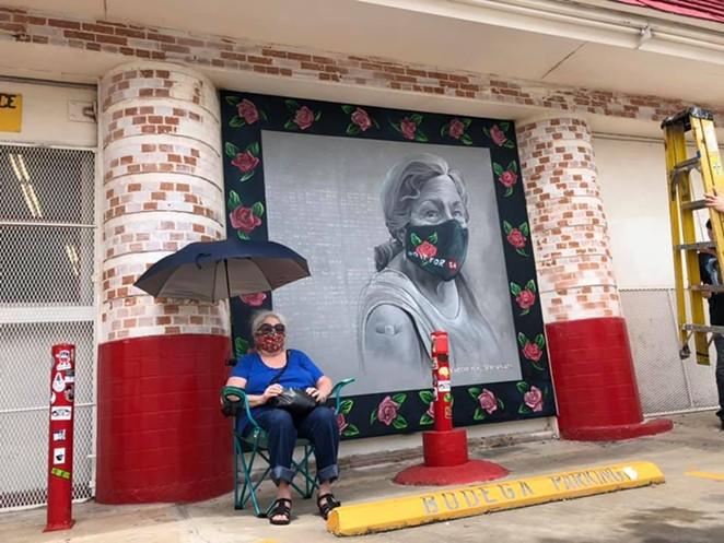 San Antonio based artist Kim Bishop's mother sits next to her daughter's mural outside of Jefferson Bodega. - FACEBOOK / JEFFERSON BODEGA