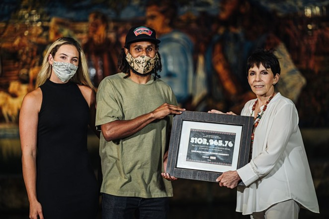 Spurs guard Patty Mills presents a $104,000 donation to Family Violence Prevention Services last year as part of a fundraiser he organized. - TWITTER / PATTY_MILLS