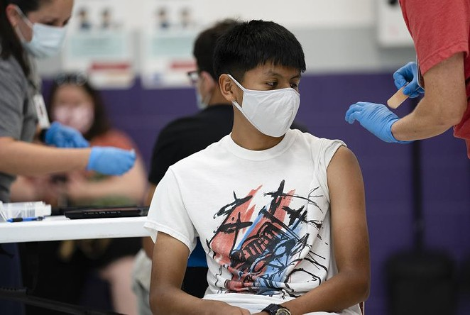 Anthony Peña, 15, sits after receiving a dose of the Pfizer vaccine at a clinic organized by the Travis County Mobile Vaccine Collaborative at Rodriguez Elementary School on July 28. - TEXAS TRIBUNE / SOPHIE PARK