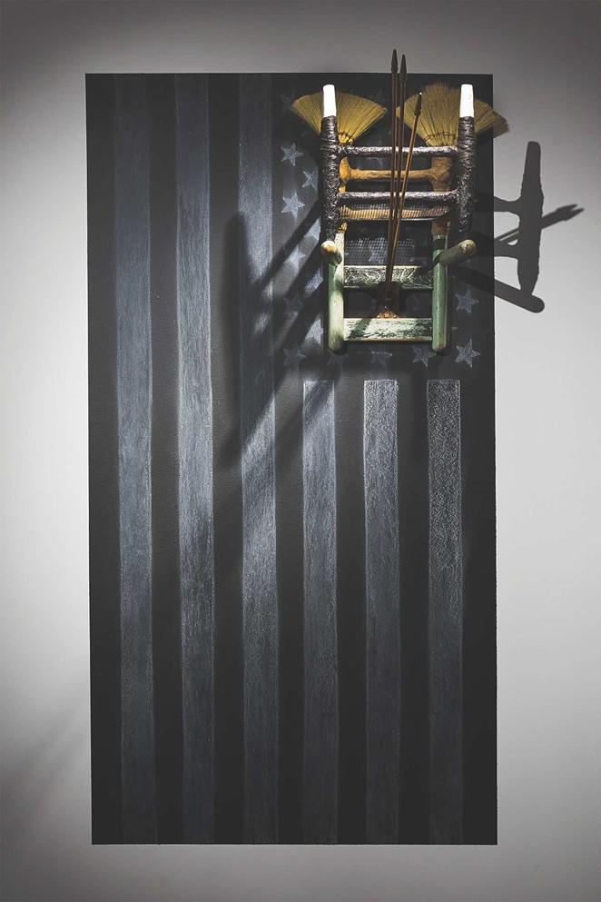 Ariel René Jackson, The next life of property, 2019, chair erected onto chalk rendering of US flag; Tampico broom corn via Mexico, Texas sourced soil, chalkboard paint, concrete, 60 x 36 x 48 in. - IMAGE COURTESY THE ARTIST. © ARIEL RENÉ JACKSON 2019.