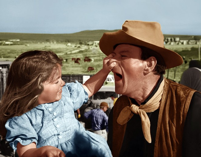 A young Aissa Wayne (left) photographed on set with her father. - COURTESY OF BRISCOE WESTERN ART MUSEUM