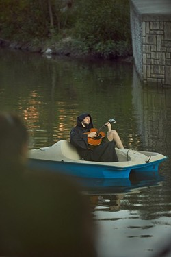 Ethan Smith plays the guitar while floating down the river. - SA HERON / TYLER SMITH