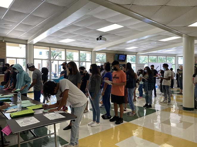 Masked students line up to register at Holmes High School in San Antonio. - TWITTER / @NISD