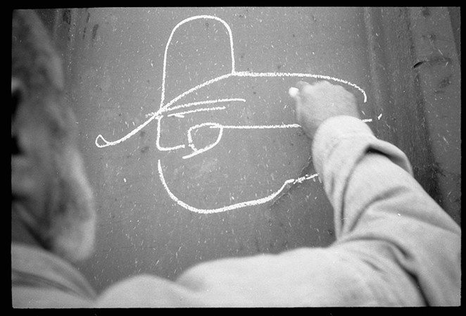 """Russell Butler's """"Colossus of Roads"""" image features a simple line-drawing profile of a trainman wearing a cowboy hat. - BILL DANIEL"""