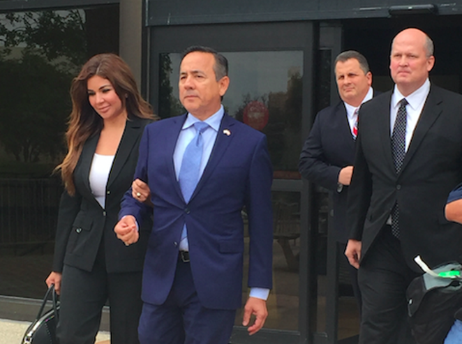 State Sen. Carlos Uresti leaves San Antonio's federal courthouse, followed by attorney Mikal Watts, after his May indictment. - ALEX ZIELINSKI