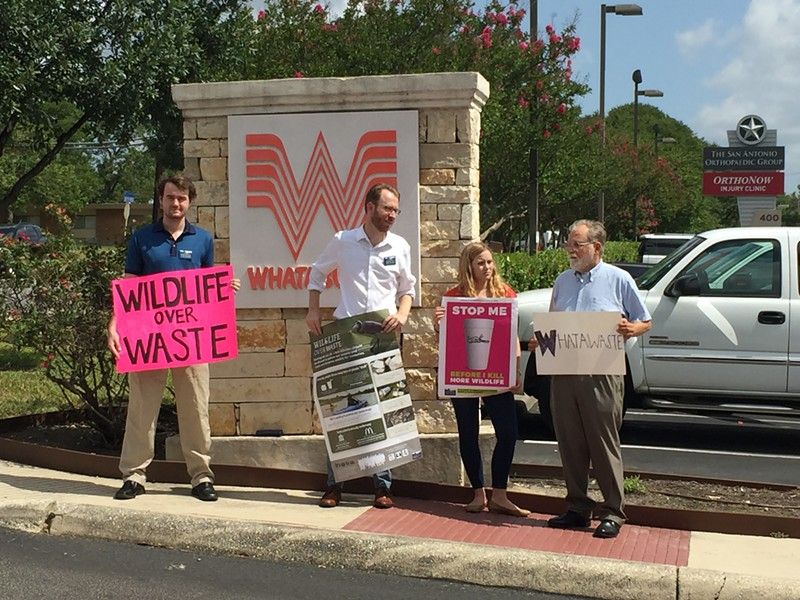 Luke Metzger (second from left) and other members of Environment Texas hold signs in front of Whataburger's S.A. headquarters. - SANFORD NOWLIN