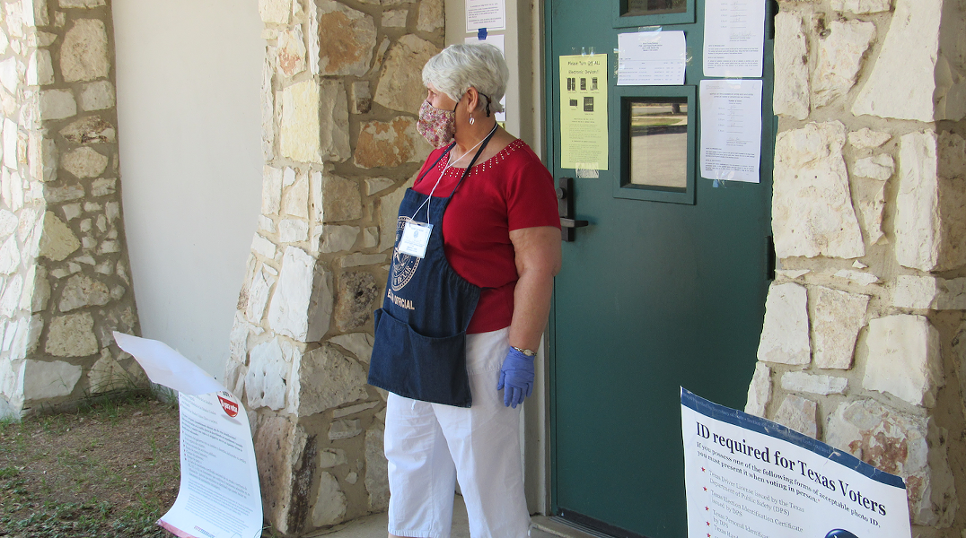 A poll worker stands outside the voting site at San Antonio's Lion's Field. - SANFORD NOWLIN