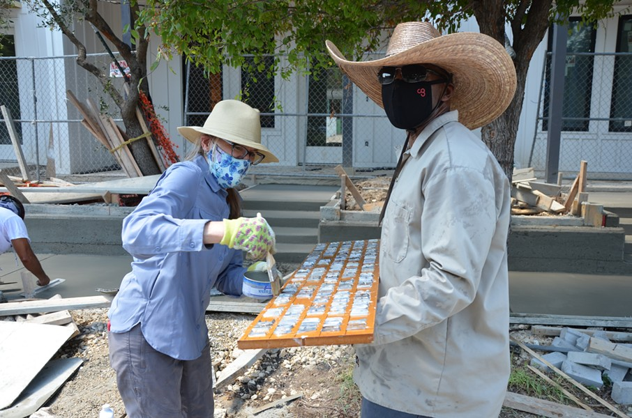 Artist Anne Wallace brushes mineral oil on a concrete stamp held by her helpful friend Antwan Nicholson. - BRYAN RINDFUSS